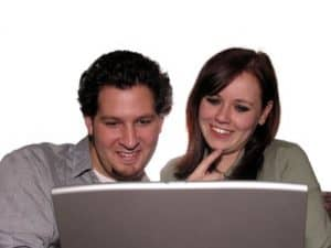 Man and Lady looking at a desk top computer